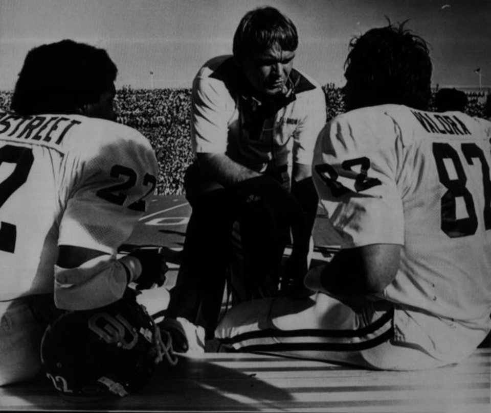Photo -  Then an OU football assistant coach, Merv Johnson talks with tight end Forrest Valora and halfback David Overstreet during a game in 1980. Johnson was at 513 consecutive games, first as an assistant, then as director of football operations and radio analyst. [THE OKLAHOMAN ARCHIVES]