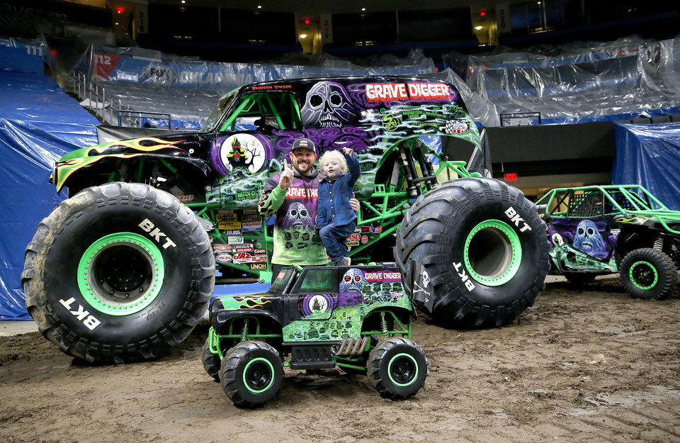 Photo - Monster Jam driver Grave Digger, Brandon Vinson, takes a picture with Ryker Ammons, 4, of Yukon, Okla., around the track at Chesapeake Energy Arena in Oklahoma City, Friday, Feb. 14, 2020.  [Sarah Phipps/The Oklahoman]