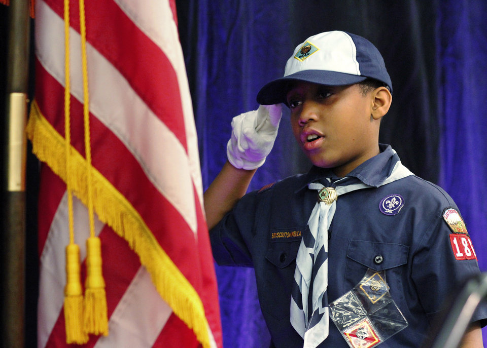 ... Photo - Cub Scout Brice Knight salutes the American flag during the posting of the colors