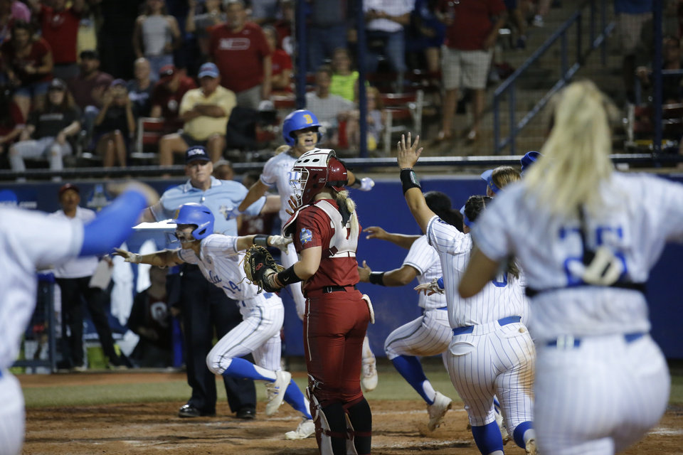 Photo - UCLA celebrates after scoring the winning run in the bottom of the seventh inning of a 5-4 victory against Oklahoma in Game 2 of the Women's College World Series championship series Tuesday at USA Softball Hall of Fame Stadium. [SARAH PHIPPS/THE OKLAHOMAN]