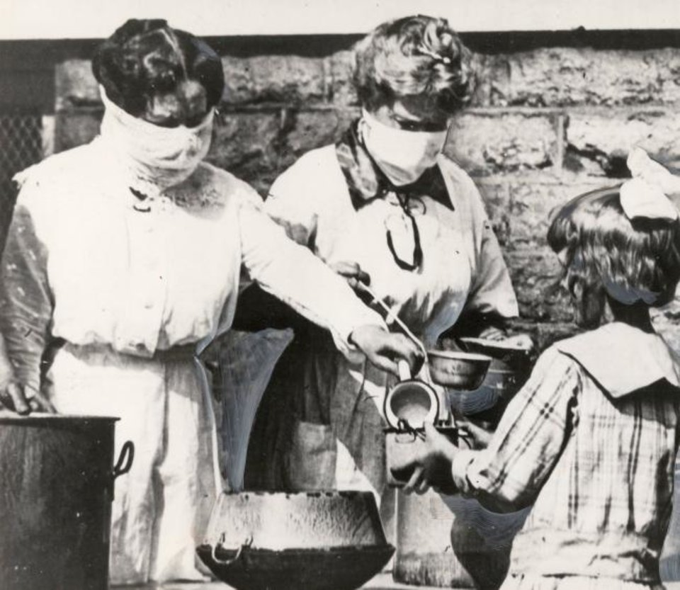 Photo -  This photo, from the Bettmann Archive, is a scene from Cincinnati in 1918. Volunteers wear gauze masks at a street kitchen while serving food to children of families afflicted by the worldwide flu epidemic of the 1918-1919 winter. [BETTMANN ARCHIVE]