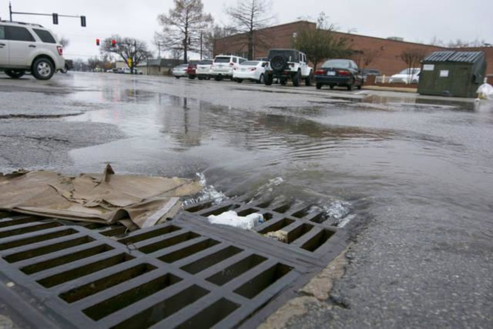 Photo - Trash clogs up a drain in downtown Edmond during a recent rain. Photo by Eriech Tapia, for The Oklahoman