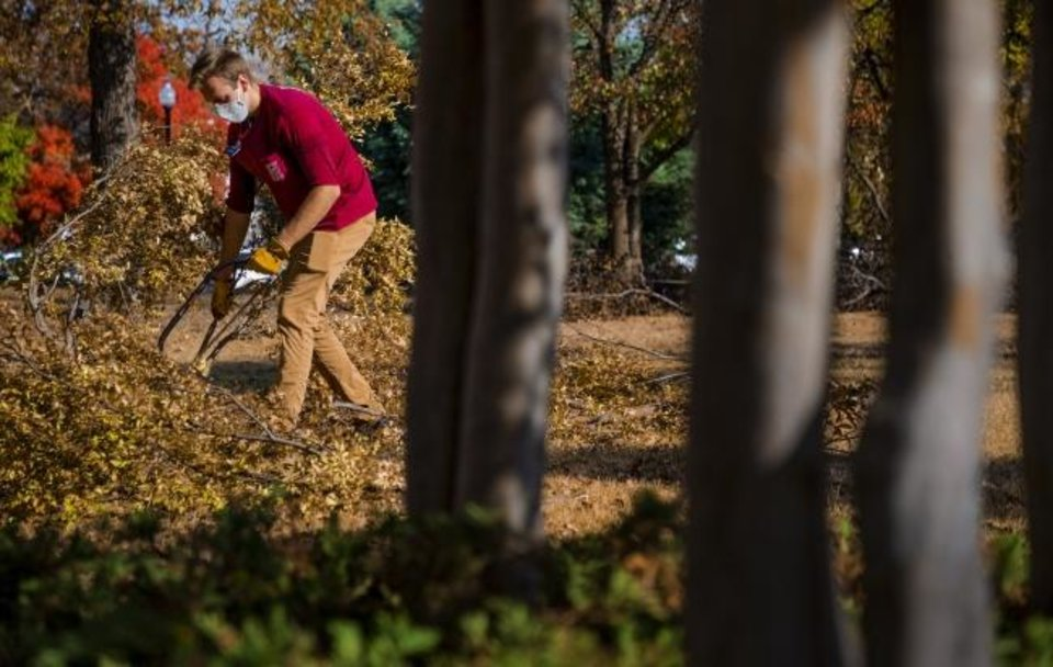 Photo -  Dane Magleby, a missionary with the Church of Jesus Christ of Latter-day Saints, cleans up at Pearl Mesta Park on Friday in Oklahoma City. , [Chris Landsberger/The Oklahoman]