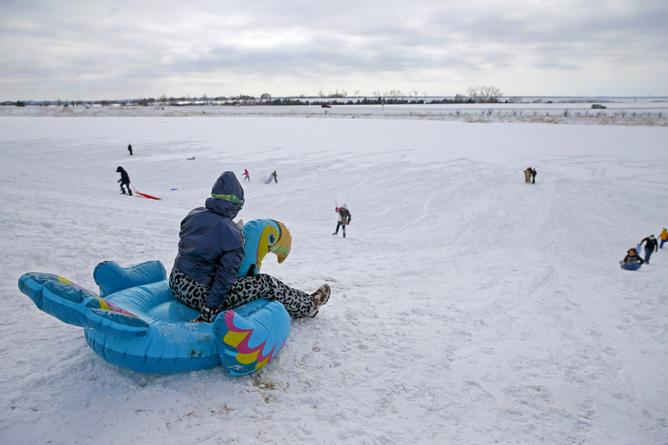 Photo - Megan Kozart gets ready to slide down a hill on an inflatable bird along W Hefner Road in Oklahoma City after a winter storm dropped another layer of snow in Oklahoma City, Wednesday, Feb. 17, 2021. [Bryan Terry/The Oklahoman]