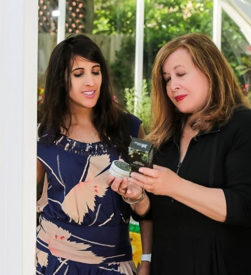 Photo -  Mallory Musallam, director of communications and marketing for the newly released CBD-oil-infused beauty product lines, Sweet Mary Jane and Beard Balm, visits with her mother, Dee Morales, about the family business at a local greenhouse. [Photo provided]
