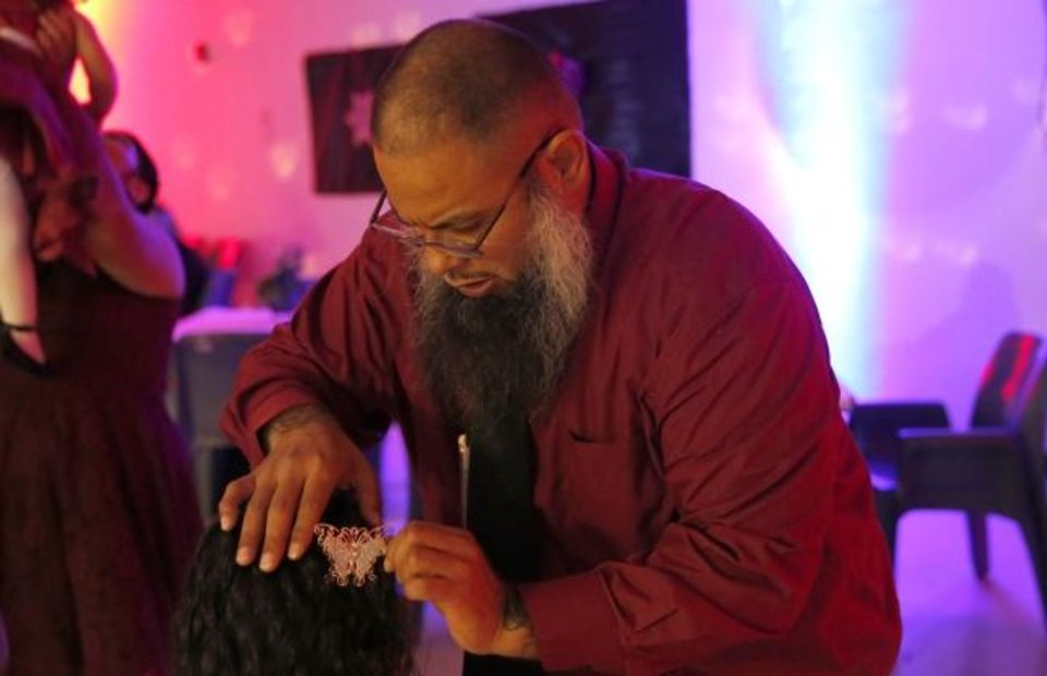 Photo -  Noel Pando fixes the bow in his daughter's hair at a Daddy-Daughter Social at Oklahoma City Transitional Living Center, a private community correctional center in Oklahoma City. [Sarah Phipps/The Oklahoman]