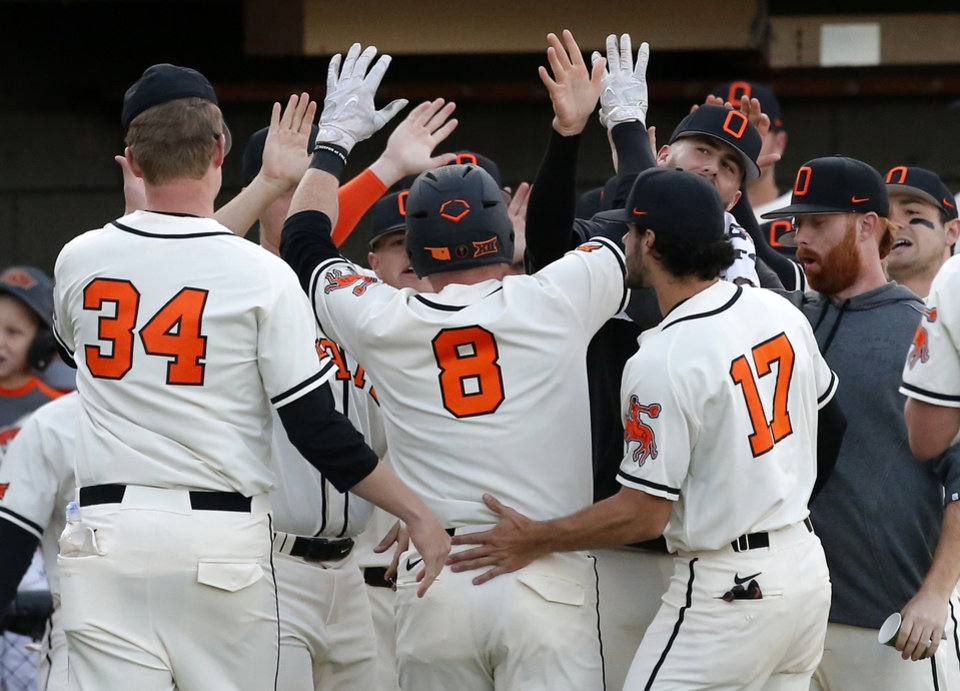 Photo - Oklahoma State celebrates a Bryce Carter (8) score in the second inning  during the Bedlam baseball game between Oklahoma State and Oklahoma at Allie P. Reynolds Stadium in Stillwater, Okla., Tuesday, March 26, 2019. On Sunday, Carter delivered a three-run home run for the Cowboys to lift OSU to a win over Oklahoma. Photo by Sarah Phipps, The Oklahoman