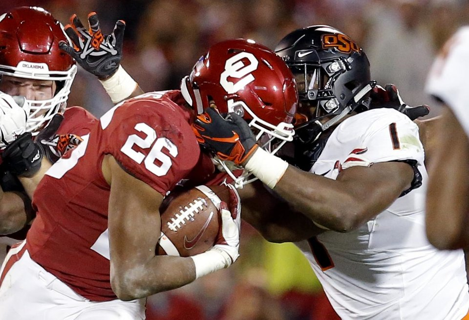 Photo - Oklahoma's Kennedy Brooks (26) tries to get free from Oklahoma State's Calvin Bundage (1) during a Bedlam college football game between the University of Oklahoma Sooners (OU) and the Oklahoma State University Cowboys (OSU) at Gaylord Family-Oklahoma Memorial Stadium in Norman, Okla., Nov. 10, 2018.  OU won 48-47. Photo by Sarah Phipps, The Oklahoman