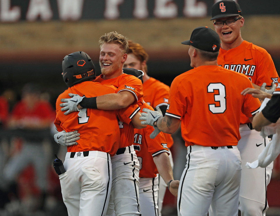 Photo - Oklahoma State players celebrate after Noah Sifrit (14) scored the game-winning run during the ninth inning in Game 2 of the team's NCAA college baseball tournament super regional against Texas Tech, Saturday, June 8, 2019, in Lubbock, Texas. (AP Photo/Brad Tollefson)