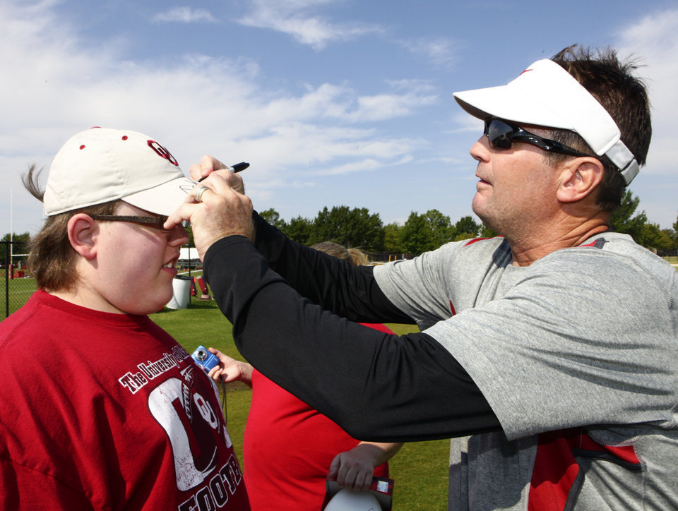 Photo - OU: University of Oklahoma college football head coach Bob Stoops, right, signs the hat of Special Olympian Tyler Bauer, 15, from Lawton, after practices, Monday, August 15, 2011.  Photo by David McDaniel, The Oklahoman  ORG XMIT: KOD