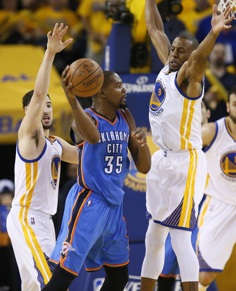 Photo - Oklahoma City's Kevin Durant (35) passes away from Golden State's Andre Iguodala (9), right, and Klay Thompson (11) during Game 2 of the Western Conference finals in the NBA playoffs between the Oklahoma City Thunder and the Golden State Warriors at Oracle Arena in Oakland, Calif., Wednesday, May 18, 2016. Golden State won 118-91. Photo by Nate Billings, The Oklahoman