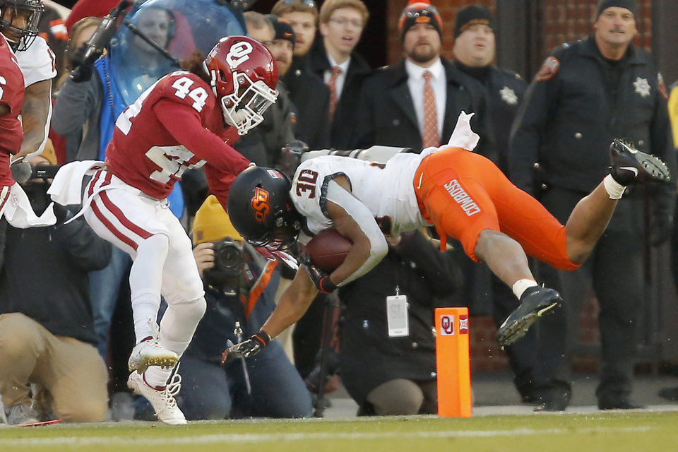 Photo - Oklahoma's Brendan Radley-Hiles (44) brings down Oklahoma State's Chuba Hubbard (30) during a Bedlam college football game between the University of Oklahoma Sooners (OU) and the Oklahoma State University Cowboys (OSU) at Gaylord Family-Oklahoma Memorial Stadium in Norman, Okla., Nov. 10, 2018.  Photo by Bryan Terry, The Oklahoman