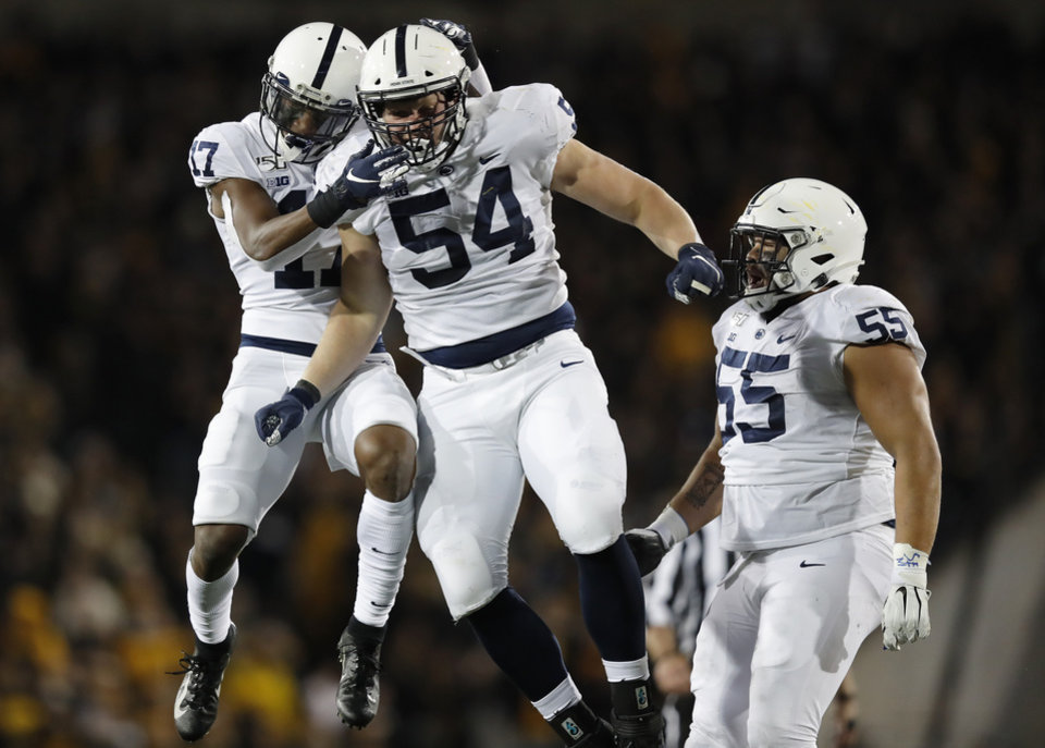 Photo - Penn State defensive tackle Robert Windsor, center, celebrates a sack with safety Garrett Taylor, left, and defensive tackle Antonio Shelton, right, during the second half of an NCAA college football game against Iowa, Saturday, Oct. 12, 2019, in Iowa City, Iowa. (AP Photo/Matthew Putney)