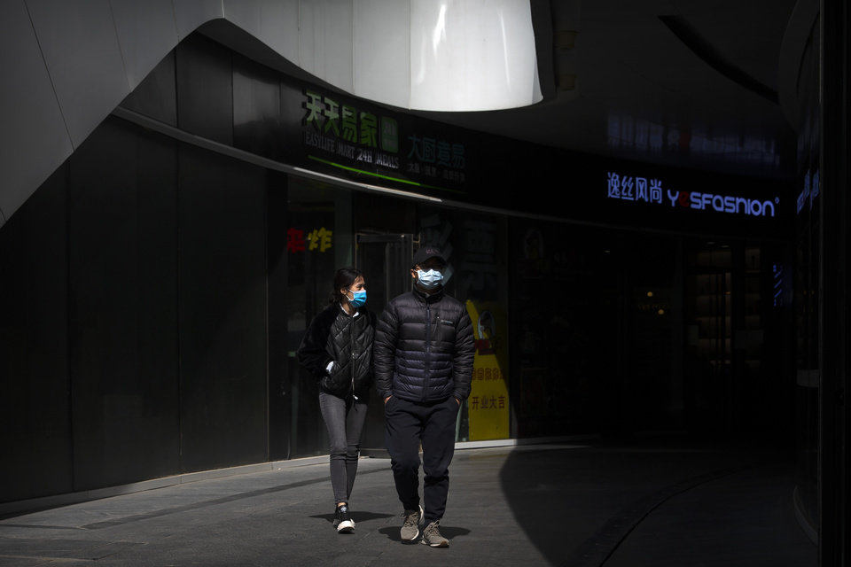 Photo -  People wear face masks as they walk through an office complex in Beijing, Friday, March 20, 2020. Italy's deaths from the coronavirus pandemic eclipsed China's on Thursday as the scourge extended its march across the West, where the United States and other countries increasingly enlisted the military to prepare for an onslaught of patients and California's governor ordered people in the most-populous U.S. state to stay home. The virus causes only mild or moderate symptoms, such as fever and cough, for most people, but severe illness is more likely in the elderly and people with existing health problems. (AP Photo/Mark Schiefelbein)