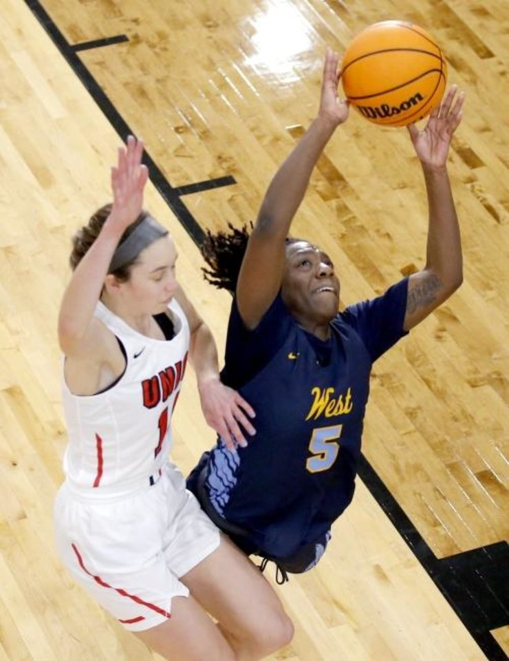 Photo -  Putnam City West's Sharonica Hartsfield shoots as Union's Makenzie Malham defends during Saturday's title game in the  Putnam City Invitational at Putnam City High School. [Sarah Phipps/The Oklahoman]