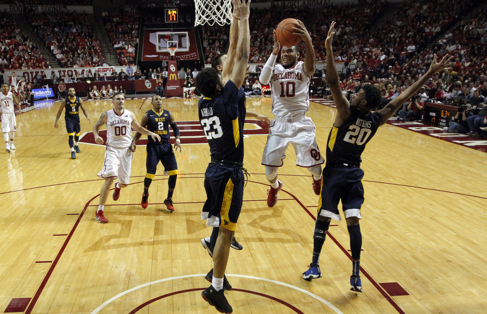 Photo - Oklahoma's Jordan Woodard (10) shoots guarded by West Virginia's Esa Ahmad (23) and Brandon Watkins (20) as the University of Oklahoma Sooner (OU) men defeat the West Virginia Mountaineers (WV) 70-68 in NCAA, college basketball at The Lloyd Noble Center on Jan. 16, 2016 in Norman, Okla. Photo by Steve Sisney, The Oklahoman