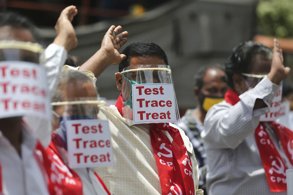 Photo -  Activists of the Communist Party of India Marxist display placards on face shields and shout slogans during a protest asking the state government to increase testing and free treatment for all COVID-19 patients, Monday, in Hyderabad, India. [Mahesh Kumar A./The Associated Press]