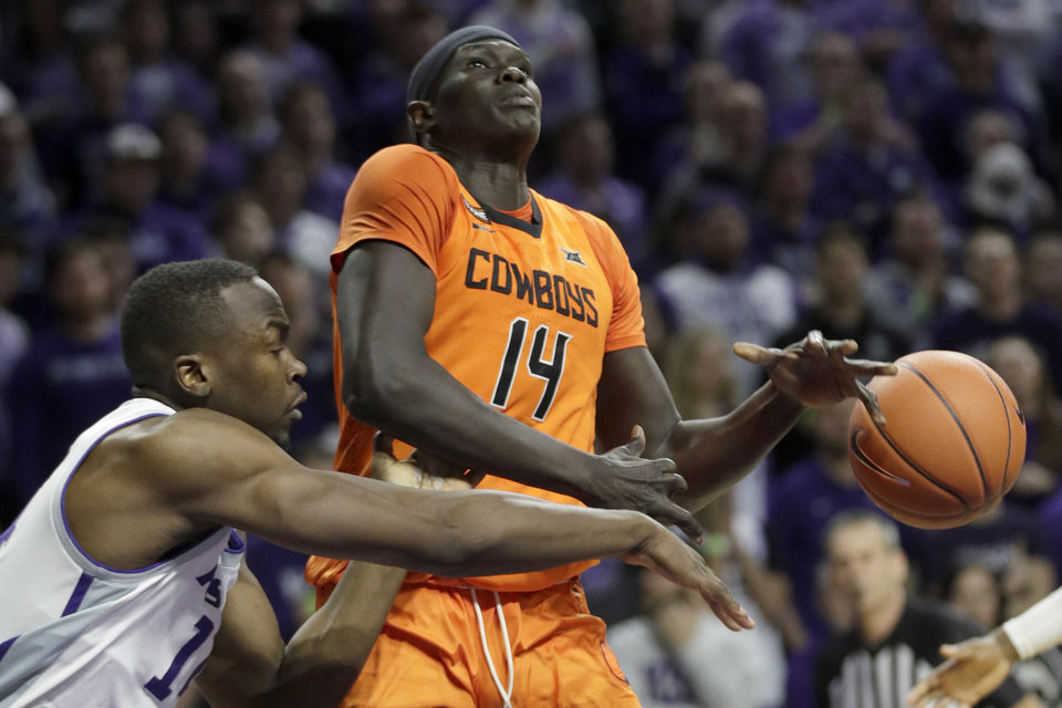 Photo - Kansas State forward Makol Mawien, left, knocks the ball away from Oklahoma State forward Yor Anei, right, during the first half of an NCAA college basketball game in Manhattan, Kan., Tuesday, Feb. 11, 2020. (AP Photo/Orlin Wagner)