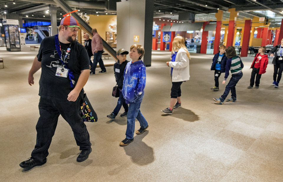 Photo - Instructor Lane Pierce walks backwards with students as they make their way to the classroom for the day camp at Science Museum Oklahoma in Oklahoma City, Okla. on Monday, April 2, 2018.  The camps are available for state students that are out of school during the teacher walkout.   Photo by Chris Landsberger, The Oklahoman