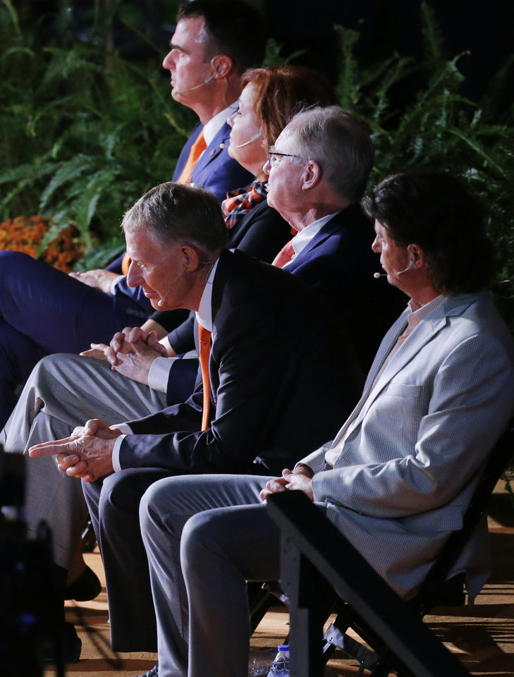 Photo - Oklahoma State athletic director Mike Holder leans forward in his chair before his turn to speak as he sits on stage with, from front, OSU football coach Mike Gundy, OSU president Burns Hargis, OSU philanthropist Anne Greenwood and Gov. Kevin Stitt, during the Celebration of Life for OSU alumnus and benefactor T. Boone Pickens at Gallagher-Iba Arena in Stillwater, Okla., Wednesday, Sept. 25, 2019. [Nate Billings/The Oklahoman]