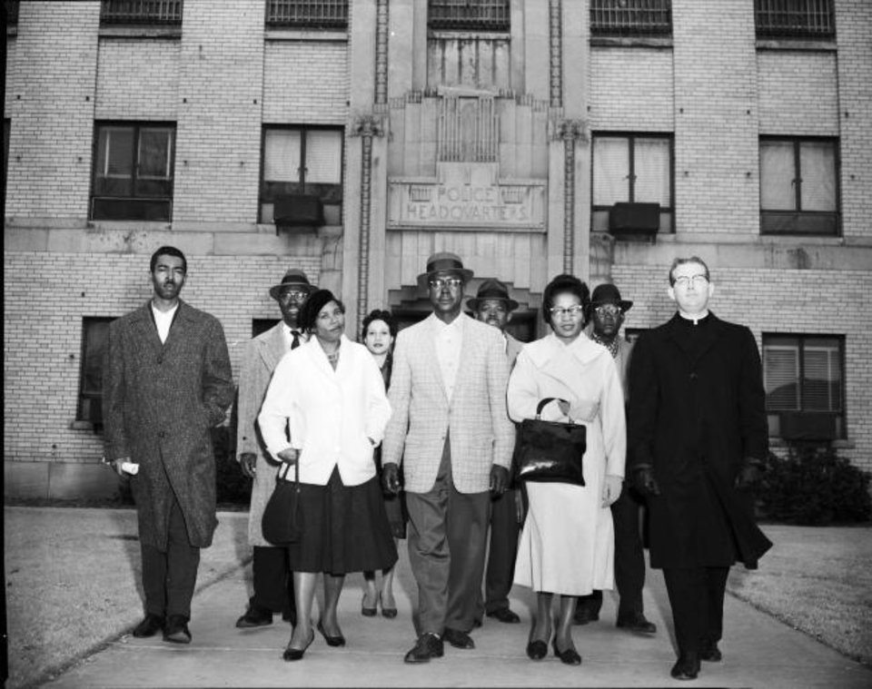 Photo -  Civil rights protesters led by E. Melvin Porter, Clara Luper and priest Robert McDone are seen in this undated photo leaving the Oklahoma City Police Headquarters. [Oklahoma History Center]