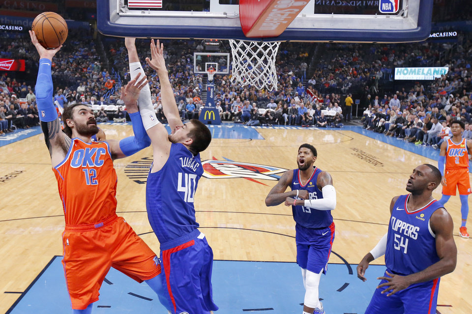 Photo - Oklahoma City's Steven Adams (12) puts up a shot beside LA's Ivica Zubac (40) during an NBA basketball game between the Oklahoma City Thunder and the LA Clippers at Chesapeake Energy Arena in Oklahoma City, Sunday, Dec. 22, 2019. Oklahoma City won 118-112. [Bryan Terry/The Oklahoman]