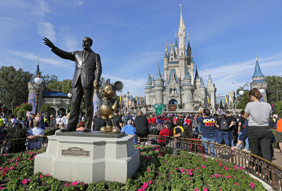 Photo - In this Jan. 9, 2019 photo, guests watch a show near a statue of Walt Disney and Micky Mouse in front of the Cinderella Castle at the Magic Kingdom at Walt Disney World in Lake Buena Vista, part of the Orlando area in Fla. [AP Photo/John Raoux, File]