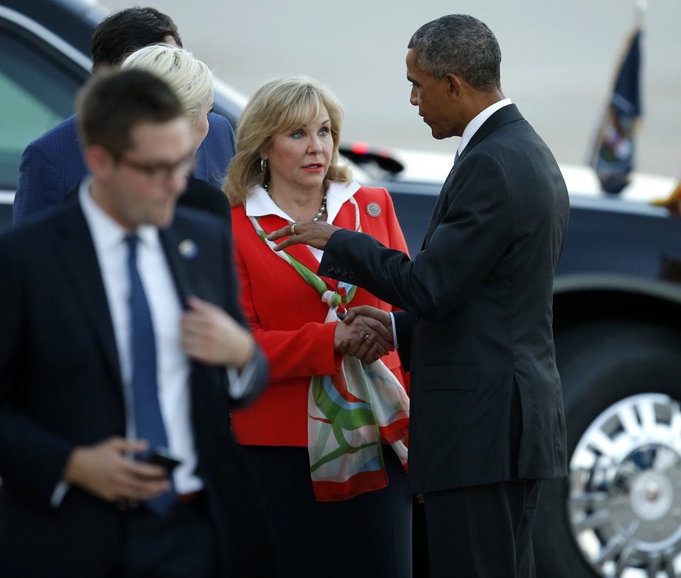Photo - President Barack Obama talks with Gov. Mary Fallin after areiving on Air Force One at Tinker Air Force Base in Midwest City, Wednesday, July 15, 2015. President Barack Obama will visit the Federal Correctional Institution El Reno, where he will meet with Oklahoma law enforcement officials and inmates and conduct an interview for a documentary scheduled to air in the fall. Photo by Bryan Terry, The Oklahoman