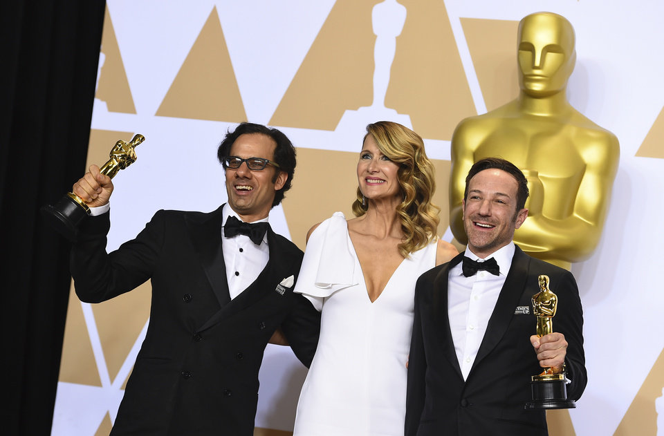"Photo - Presenter Laura Dern, center, poses with Dan Cogan, left, and Bryan Fogel, winners of the award for best documentary feature for ""Icarus,"" in the press room at the Oscars on Sunday, March 4, 2018, at the Dolby Theatre in Los Angeles. (Photo by Jordan Strauss/Invision/AP)"