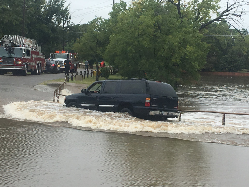Firefighters rescue woman whose SUV was stuck in water in ...