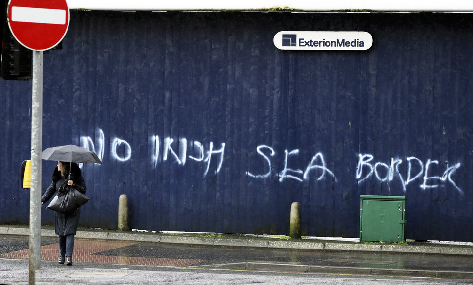 Photo -  A woman walks past past graffiti with the words 'No Irish Sea Border' in Belfast city centre, Northern Ireland, Wednesday, Feb. 3, 2021. Politicians from Britain, Northern Ireland and the European Union are meeting to defuse post-Brexit trade tensions that have shaken Northern Ireland's delicate political balance. British Cabinet minister Michael Gove, European Commission Vice President Maros Sefcovic and the leaders of Northern Ireland's Catholic-Protestant power-sharing government will hold a video conference to discuss problems that have erupted barely a month after the U.K. made an economic split from the 27-nation EU. (AP Photo/Peter Morrison)