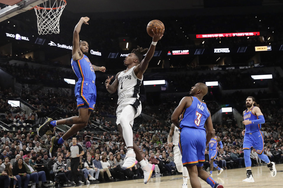 Photo - San Antonio Spurs guard Lonnie Walker IV (1) drives to the basket against Oklahoma City Thunder guard Terrance Ferguson (23) during the second half of an NBA basketball game, in San Antonio, Thursday, Jan. 2, 2020. Oklahoma City won 109-103. (AP Photo/Eric Gay)