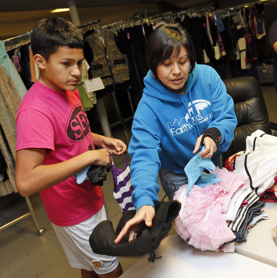 Photo - Vicky Primeaux, right, a FaithWorks of the Inner City employee, and Sixto Kirk,a student in the ministry's work training program, sort clothes at the new Shidler-Wheeler Community Thrift Store, 735 SE 15.   NATE BILLINGS - NATE BILLINGS