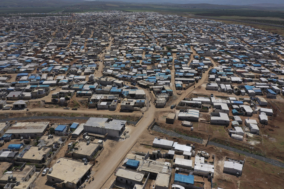 Photo -  FILE - This April 19, 2020 file photo shows a large refugee camp on the Syrian side of the border with Turkey, near the town of Atma, in Idlib province, Syria. The head of the U.N. food agency warned of starvation and another wave of mass migration from Syria to Europe unless donors countries step up financial assistance to the war-ravaged country. (AP Photo/Ghaith Alsayed, File)