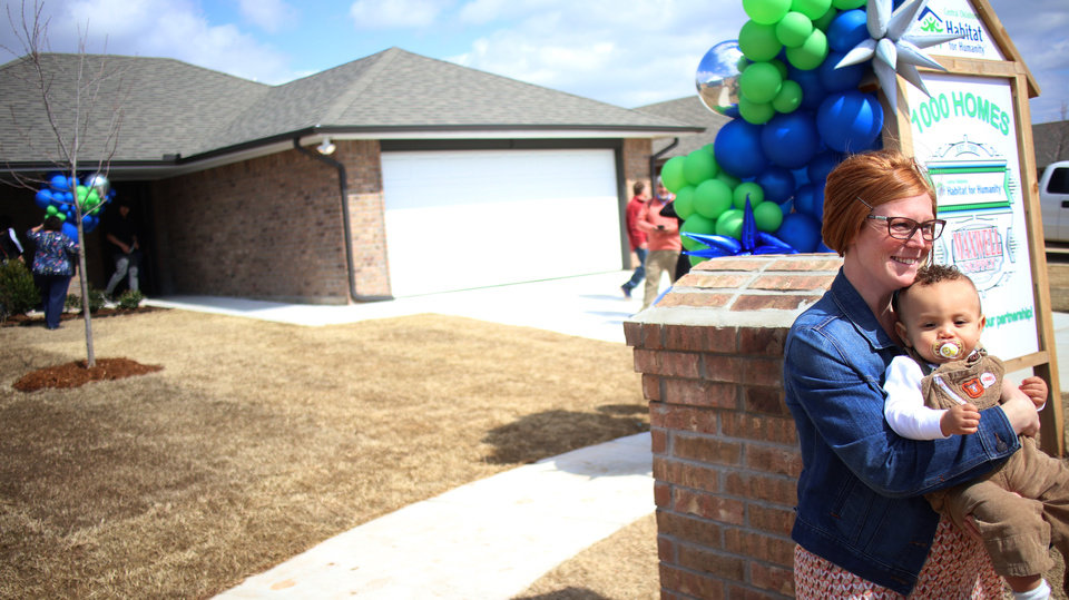 Photo - Brittani Githiri holds her son, Piaget, 1, by the mailbox of her new home.  Habitat for Humanity's 1,000th home, Monday, March 9, 2020.  [Photo by Doug Hoke/The Oklahoman]