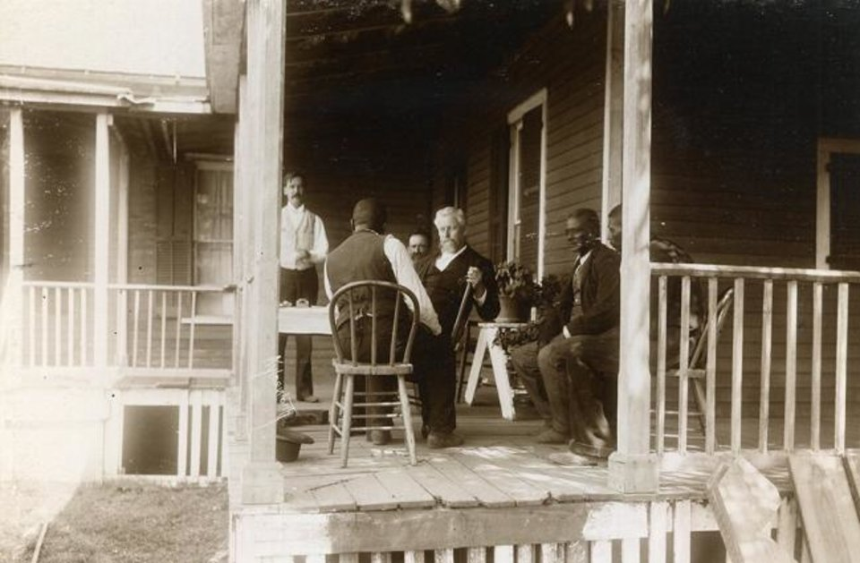 Photo -  Captain McKennon of the Dawes Commission, seated with white hair, enrolls freedmen at Fort Gibson. [Aylesworth Album Collection, OHS]