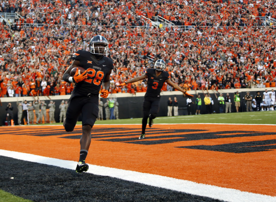 Photo - Oklahoma State's James Washington (28) scores a touchdown as Marcell Ateman (3)  celebrates in the third quarter during the college football game between the Oklahoma State Cowboys (OSU) and TCU Horned Frogs at Boone Pickens Stadium in Stillwater, Okla., Saturday, Nov. 7, 2015. Photo by Sarah Phipps, The Oklahoman