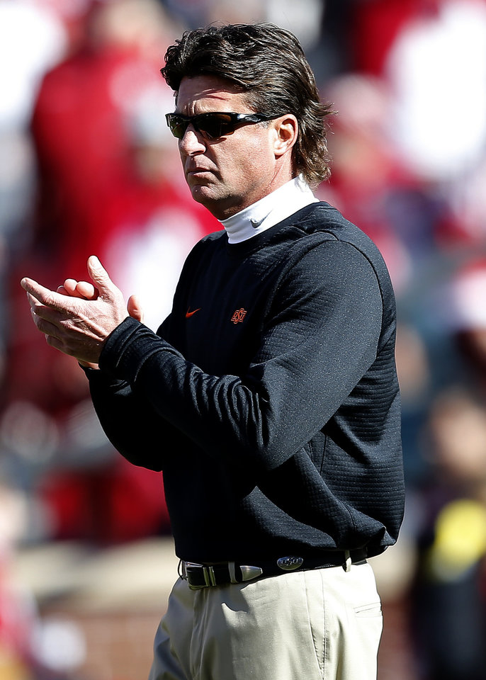 Photo - Oklahoma State head coach Mike Gundy watches his team warm up before a Bedlam college football game between the University of Oklahoma Sooners (OU) and the Oklahoma State University Cowboys (OSU) at Gaylord Family-Oklahoma Memorial Stadium in Norman, Okla., Nov. 10, 2018.  OU won 48-47. Photo by Sarah Phipps, The Oklahoman
