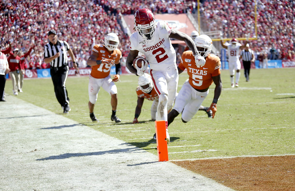 Photo - Oklahoma's CeeDee Lamb (2) runs in for a score as Brandon Jones (19), Chris Brown (15) and D'Shawn Jamison (5) defend during the Red River Showdown college football game between the University of Oklahoma Sooners (OU) and the Texas Longhorns (UT) at Cotton Bowl Stadium in Dallas, Saturday, Oct. 12, 2019. OU won 34-27. [Sarah Phipps/The Oklahoman]