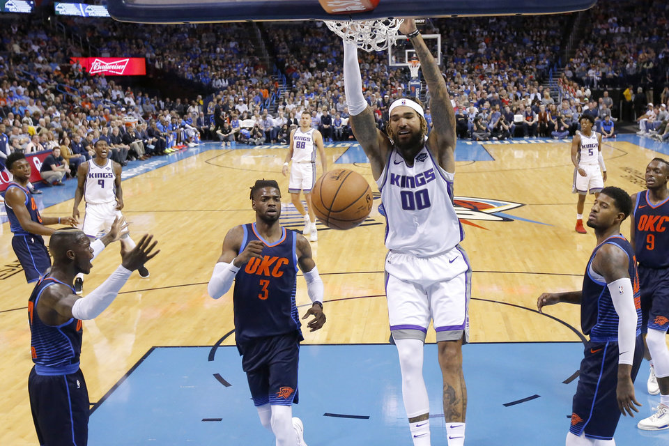 Photo - Sacramento's Willie Cauley-Stein (00) dunks the ball between Oklahoma City's Dennis Schroder (17), Nerlens Noel (3) and Paul George (13) during an NBA basketball game between the Oklahoma City Thunder and the Sacramento Kings at Chesapeake Energy Arena in Oklahoma City, Sunday, Oct. 21, 2018. Photo by Bryan Terry, The Oklahoman