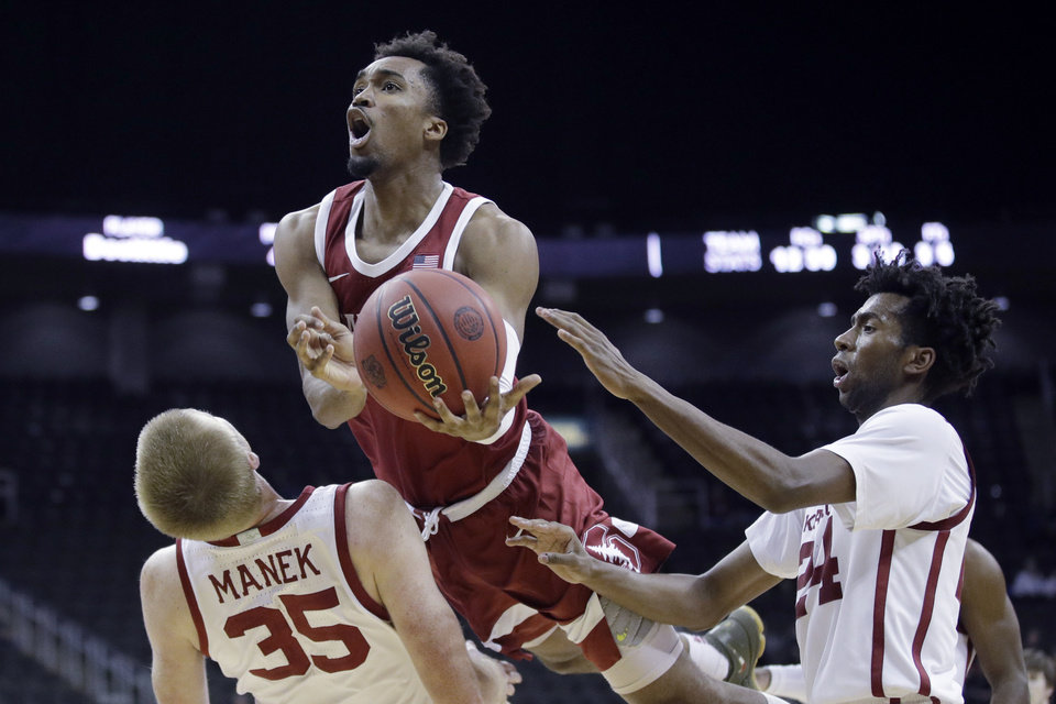 Photo - Stanford guard Bryce Wills, center, shoots between Oklahoma forward Brady Manek (35) and guard Jamal Bieniemy (24) during the second half of an NCAA college basketball game Monday, Nov. 25, 2019, in Kansas City, Mo. Stanford won 73-54. (AP Photo/Charlie Riedel)
