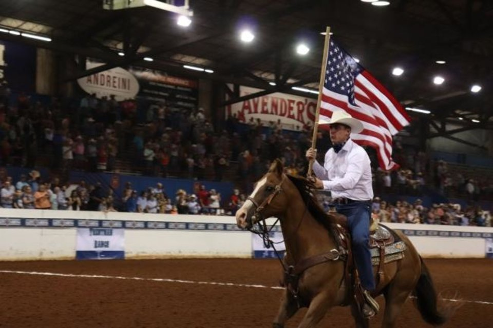 Photo -  Gov. Kevin Stitt rides in carrying the U.S. Flag at the Oklahoma Cattlemen's Association's Ranch Rodeo. [PROVIDED BY OKLAHOMA CATTLEMEN'S ASSOCIATION]