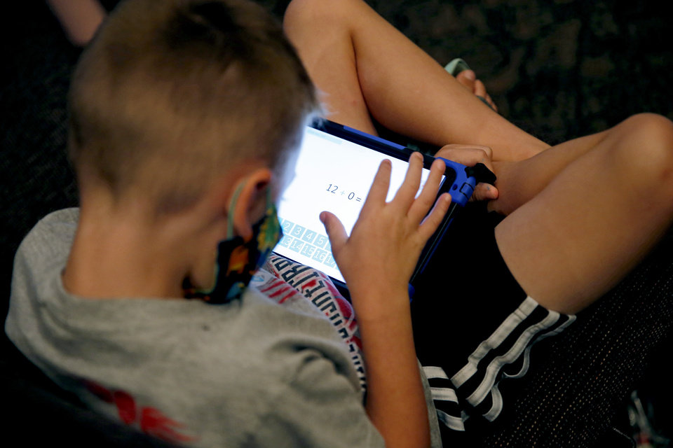 Photo - A child works on a tablet inside Henderson Hills Baptist Church in Edmond, Okla., Wednesday, Aug. 26, 2020. The church has begun offering Edmond school students a place to go on Wednesdays to get homework help, use the free wi-fi for virtual learning, free lunch and other activities. [Bryan Terry/The Oklahoman]