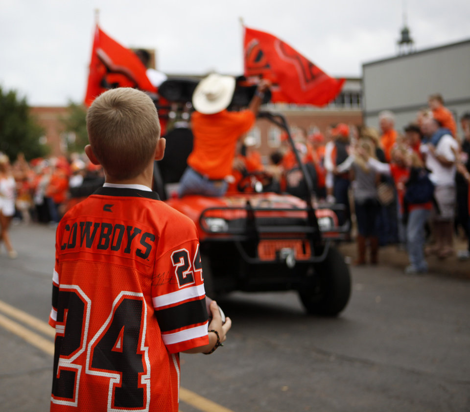 Photo - Garrick Martin, 9, of Stillwater, Okla., cheers during the Spirit Walk before the college football game between the Oklahoma State Cowboys (OSU) and the Nebraska Huskers (NU) at Boone Pickens Stadium in Stillwater, Okla., Saturday, Oct. 23, 2010. Photo by Bryan Terry, The Oklahoman