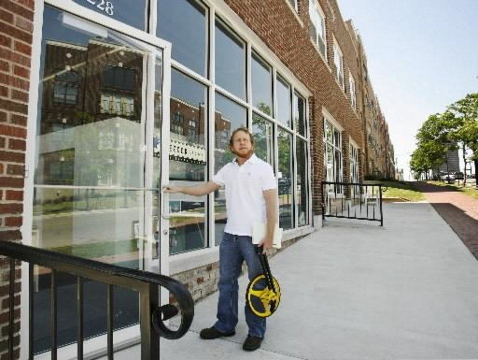 Photo -  Jeff  Bezdek stands at the front door to his office, just 250 feet east of his third floor apartment in the Deep Deuce Apartments in downtown Oklahoma City, Friday, April 21, 2006. Staff photo by Jim Beckel.