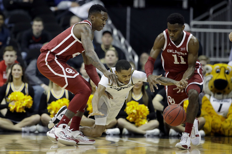 Photo -  Missouri guard Xavier Pinson, center, dives for a loose ball between Oklahoma forward Kristian Doolittle, left, and guard De'Vion Harmon during the first half of Tuesday's game in Kansas City, Mo. OU won, 77-66. [AP Photo/Charlie Riedel]