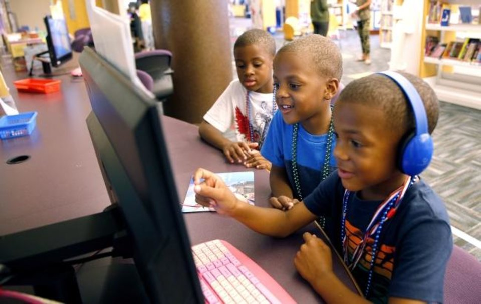 Photo -  From left, Christopher Harris, 8, Kalomo Harris,4, and JaJa Harris, 5, play computer games Tuesday in the Children's area at the Ronald J. Norick Downtown Library in Oklahoma City. [Sarah Phipps/The Oklahoman]