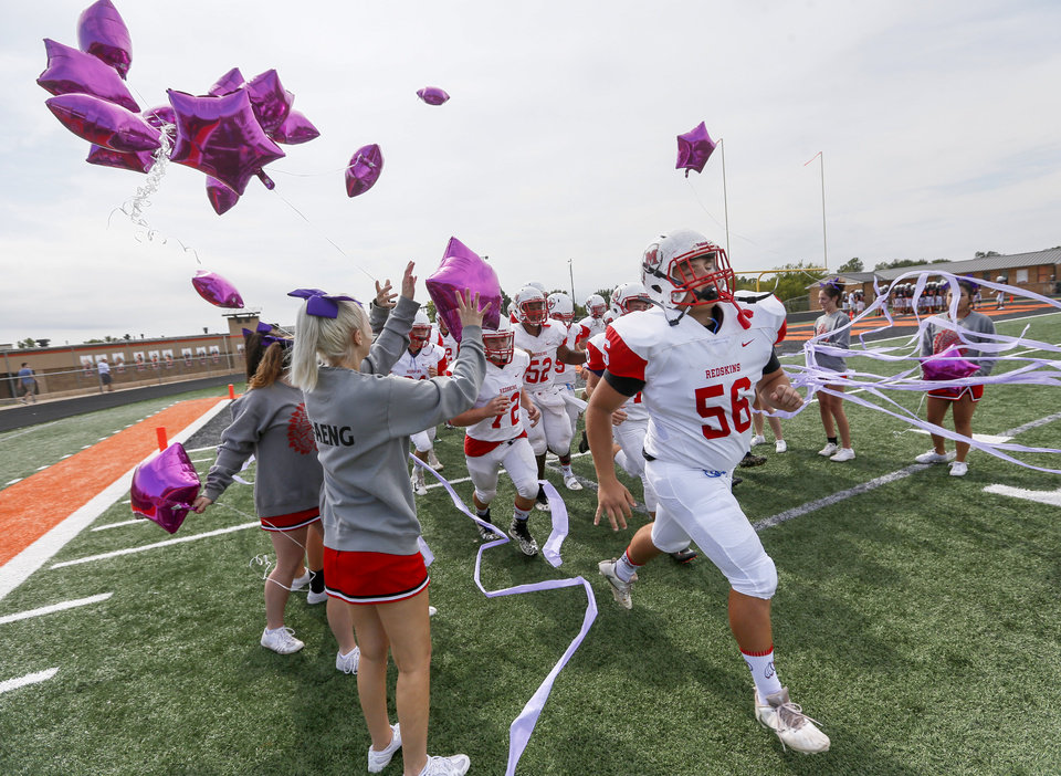 Photo - McLoud players run through purple streamers to take the field as cheerleaders release purple balloons before a high school football game between McLoud and Cushing at O'Dell Field in Cushing, Okla., Saturday, Oct. 6, 2018. The game was postponed and moved from McLoud after Kaylen Thomas, a McLoud High School student, was fatally shot the previous day. The cheerleaders brought purple streamers and balloons because they said purple was Thomas' favorite color. Photo by Nate Billings, The Oklahoman