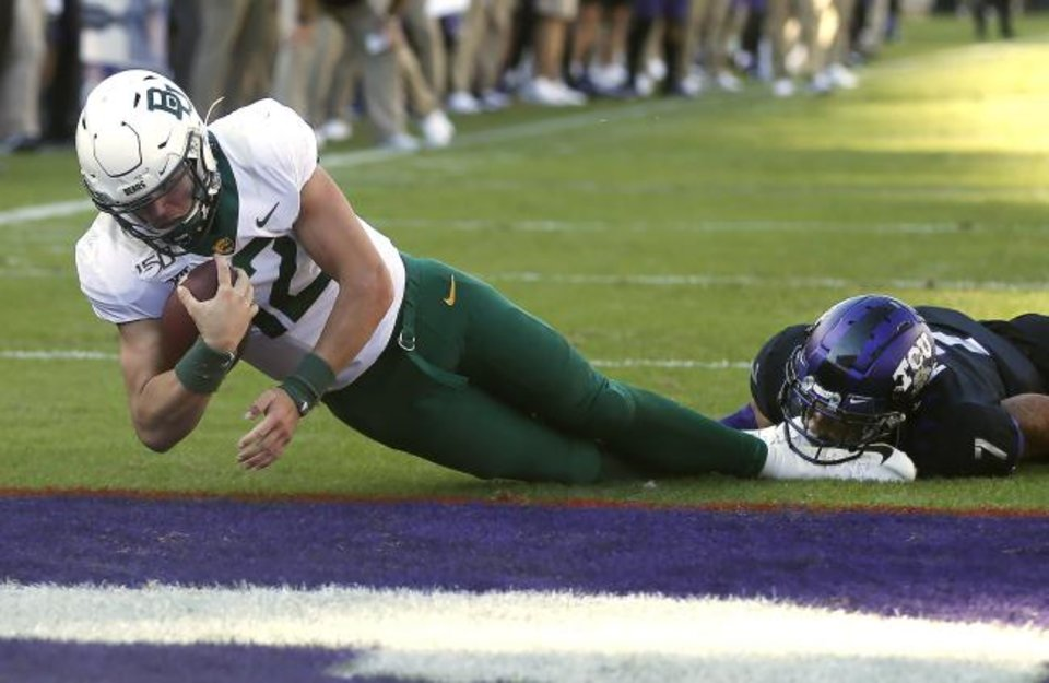 Photo -  Baylor quarterback Charlie Brewer (12) dives across the goal line to score a touchdown as TCU safety Trevon Moehrig (7) goes to the ground during Saturday's game in Fort Worth, Texas. Baylor won 29-23 in triple overtime. [AP Photo/Ron Jenkins]