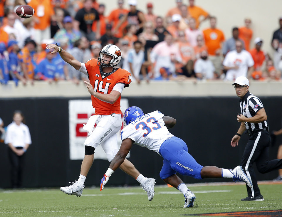 Photo - Oklahoma State's Taylor Cornelius (14) throws as he is pressured by Boise State's Tony Lashley (33) during a college football game between the Oklahoma State Cowboys (OSU) and the Boise State Broncos at Boone Pickens Stadium in Stillwater, Okla., Saturday, Sept. 15, 2018. OSU won 44-21. Photo by Sarah Phipps, The Oklahoman